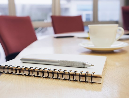 Notepad and pen on boardroom table