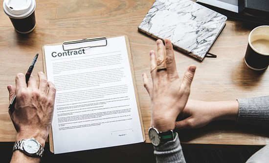 Hands above contract on clipboard