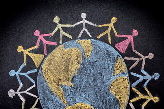 CHalkboard drawing of stick figures holding hands around globe