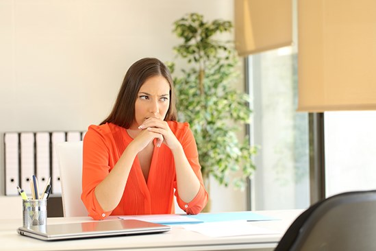 Business woman looking pensively at computer
