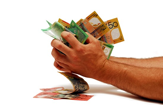 Hands holding bundles of Australian bank notes