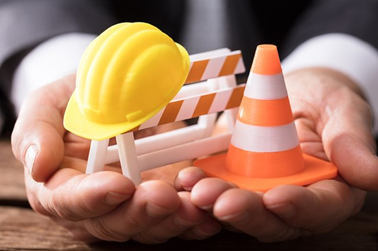 Small hard hat, construction sign and traffic cone in businessman's hands