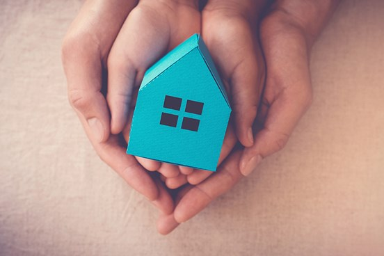 Adult and child's hands cradling a blue paper house